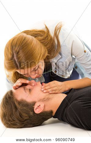 Couple demonstrating first aid techniques with woman about to perform mouth resuscitation