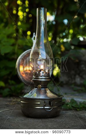 Old Kerosene Lamp Stands On The Ground, Outdoors