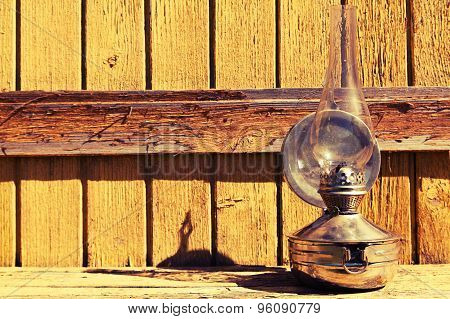 Old Kerosene Lamp Stands On Wooden Surface, Outdoors