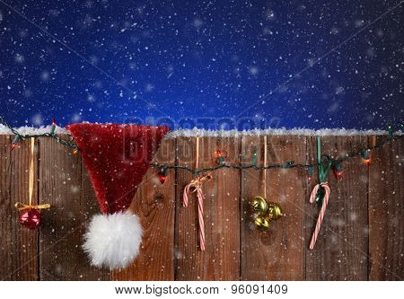 A rustic fence with christmas lights, bells, candy canes and a Santa Claus hat. Horizontal format with a light to dark blue night sky and snow effect.