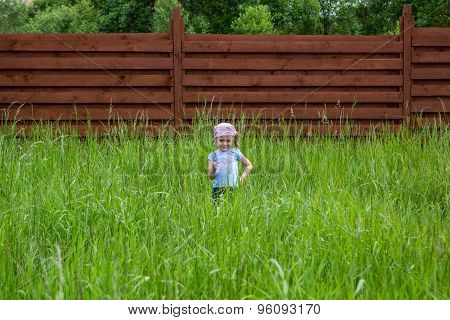 Disaffected Little Girl With Attractive Face With A Blade Of Grass In Hand