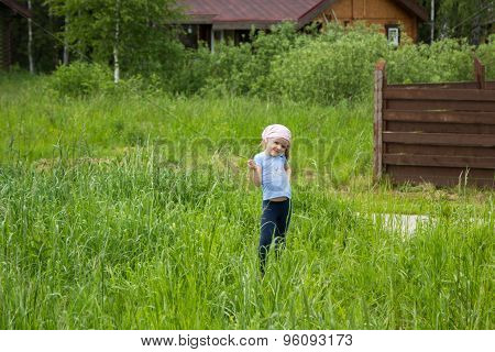 Little Girl With Blade Of Grass In Hands Makes Eyes