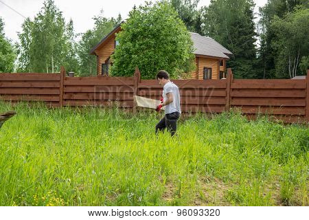 Man Carries A Wooden Board In Grass