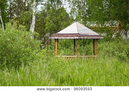 Gazebo In Thickets Of Grass And Bushes