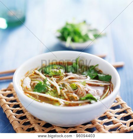 traditional pho tai beef vietnamese soup in bowl with cilantro and bean sprouts