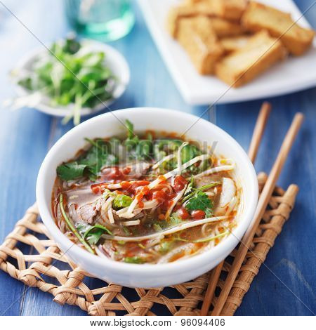 bowl of vietnamese Pho Tai beef soup with spicy sriracha sauce