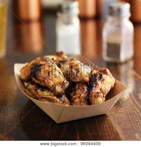 barbecued chicken wings in disposable brown paper tray