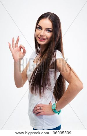 Smiling beautiful woman standing with arms folded isolated on a whtie background. Looking at camera