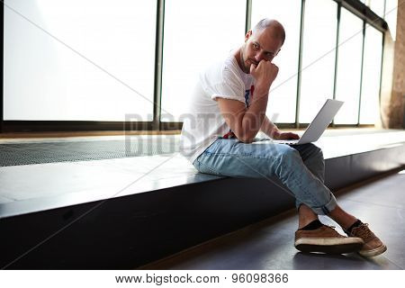 Young university student using notebook for write his coursework while sitting in modern interior