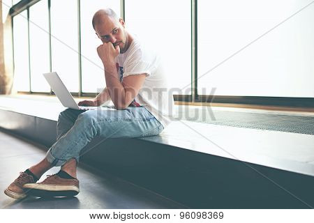Handsome man looking thoughtful while working on laptop computer holding it on the knees