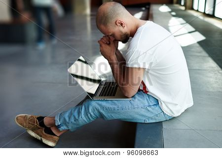 Young male freelancer with notebook sitting in modern space hall looking pensive and worried