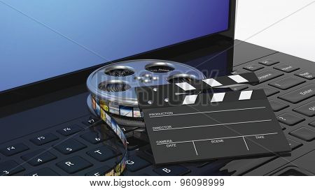 Clapperboard and film reel on black laptops keyboard
