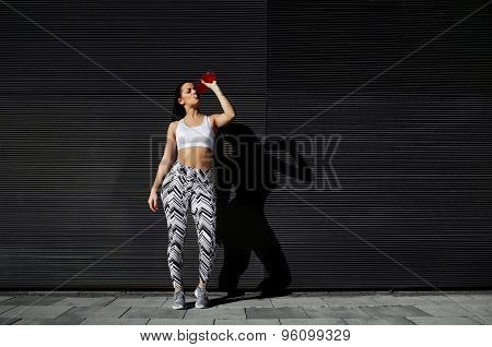 Healthy fit female runner drink while take breaking after fitness training in urban setting