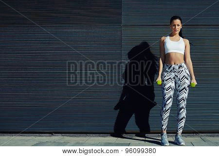 Beautiful young woman in sporty clothing training bicep curls outdoors with copy space background