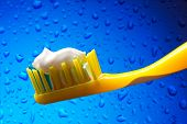 stock photo of toothpaste  - Toothbrush and toothpaste on blue water background - JPG