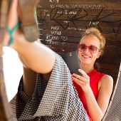 picture of casual wear  - Casually dressed young cheerful lady wearing red sunglasses playing carelessly with her android smarthphone browsing trough social networks relaxing on  contemporary circular bench in city park - JPG