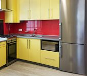foto of laminate  - yellow kitchen with cupboards with hinged doors topped with a grey worktops and fitted with appliances including refrigerator microwave oven extractor hood a wall with a red tile and floor with soft sand grey laminate - JPG