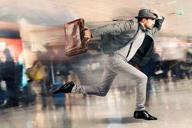 foto of aeroplan  - Late tourist man runs fast in airport - JPG