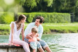 foto of jetties  - Happy family sitting on jetty on lake or pond letting feet hang into the water - JPG