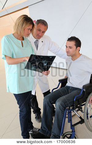 Medical team with handicapped person looking at X-ray