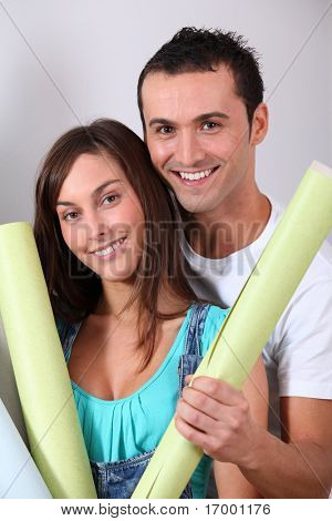 Closeup of young couple holding wallpaper rolls