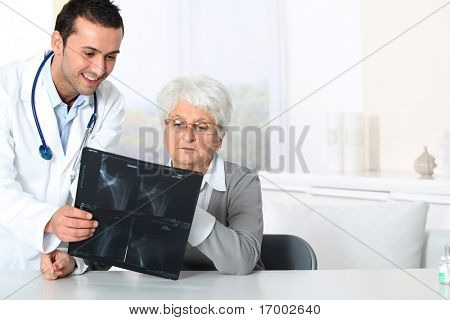 Doctor showing x-ray results to elderly woman