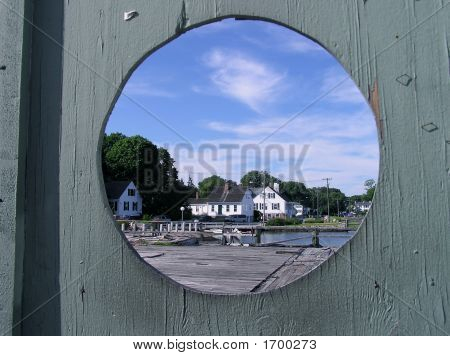 Beach House Through a Hole in a Wooden Fence