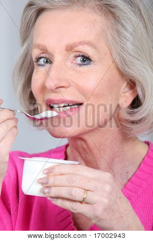 Portrait of senior woman eating yogurt