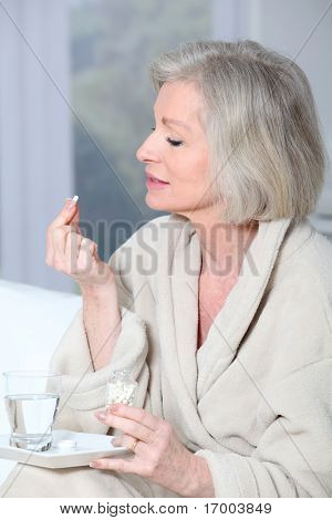 Senior woman in bathrobe taking pills