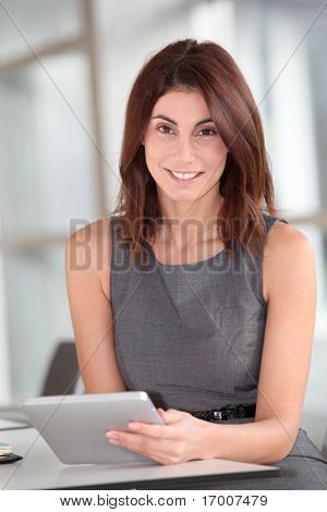 Beautiful businesswoman working on electronic tab