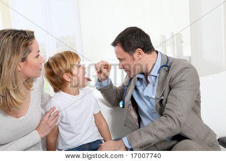 Doctor examining little boy throat