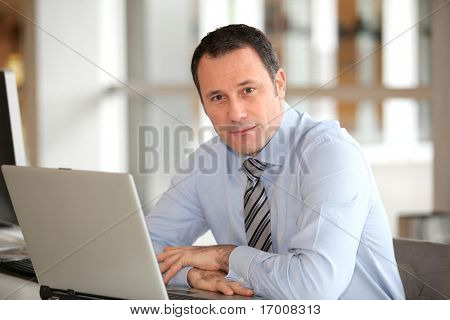 Portrait of businessman in front of laptop computer