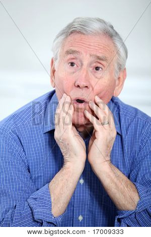 Portrait of surprised elderly man