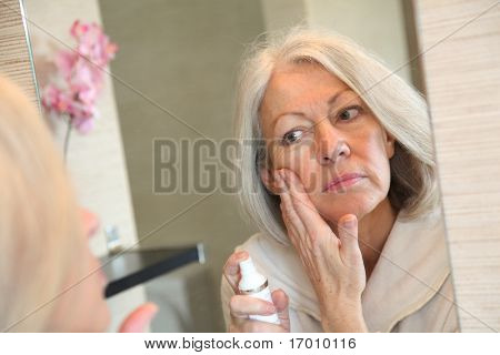 Senior woman applying moisturizer on her face