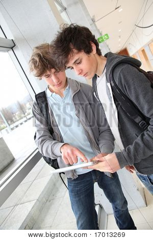 Teenage boys using electronic tablet in school hall
