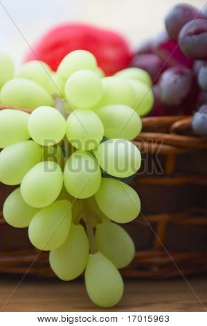 Red and white grape branch in a basket.