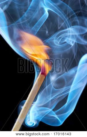 Photo of a burning match in a smoke on a black background
