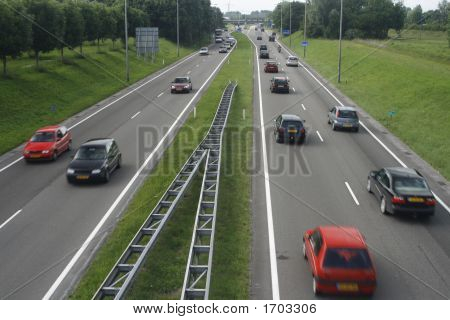 Cars On Highway With Green Patch In Between The Lanes