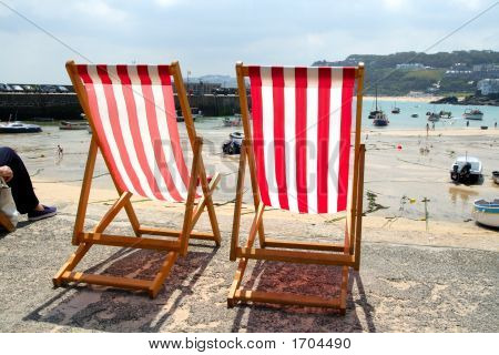 Two Empty Deckchairs On The Sea Front, St. Ives, Uk.