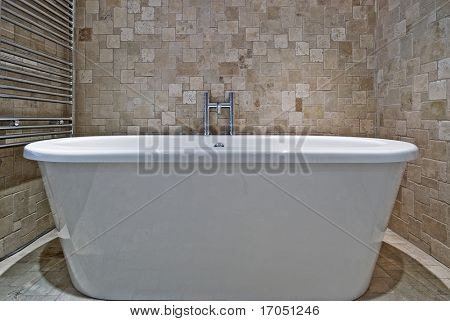 free standing contemporary ceramic bath tub and stone tile wall