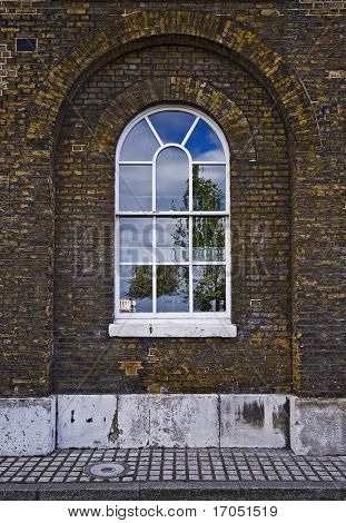 yellow brick arched warehouse window with white frame