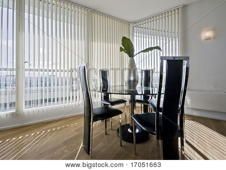 stylish modern dining room with a round glass top table and seats for five