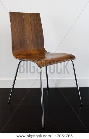 modern designer chair with stainless steel legs and steam bended wood backrest