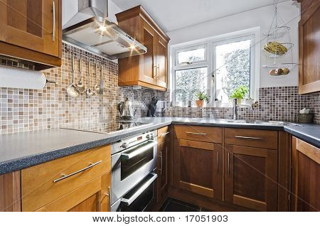 classic domestic kitchen with wooden counter and stone imitation worktop