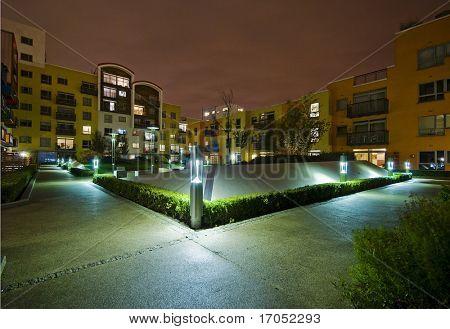 modern development with communal garden after dark