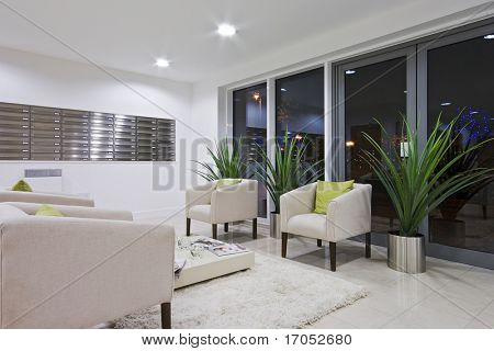 hallway of a modern development with post room and sofas
