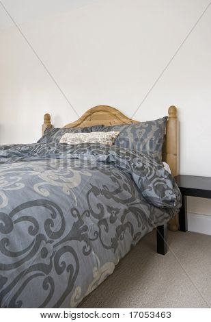 double bed with hard wood bed frame and abstract motif bedsheets