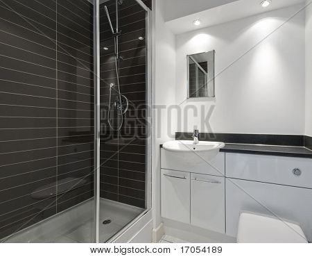 modern en-suite bathroom with a shower cabin and dark ceramic tiles