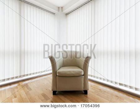 beige leather armchair in a room with wooden floor and vertical blinds