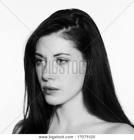 studio shot portrait of a Young woman crying on white isolated background in balck and white